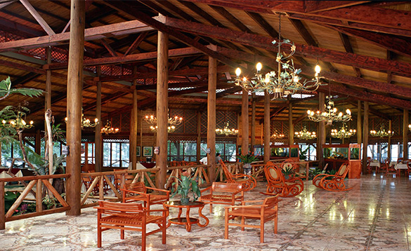 large open seating area with red wood tables and chairs, tiled floors, wooden pillars and ceiling with chandeliers/