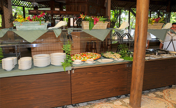 buffet counter with plates and a selection of food on display/