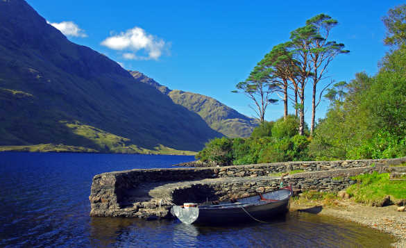 Rowing boat moored against a stone jetty on Doo Lough, Co Mayo/