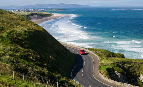 Car travelling along the coast road in Co Antrim past waves breaking against sandy beaches/