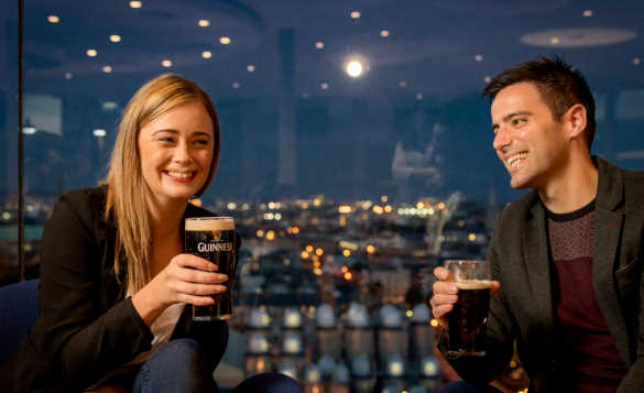 Couple enjoying a pint of Guinness in the Gravity bar at the Guinness Storehouse with views across Dublin at night/