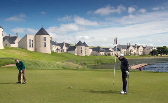 Golfers putting on a green surrounded by bunkers in front of the Lough Erne Golf Resort Hotel/