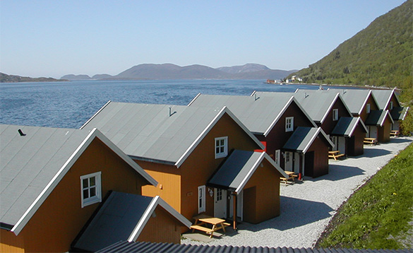 row of orange cabins standing along the edge of a fjord with mountains in the distance/