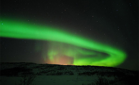 nightime sky with impressive show of the northern lights, bright green arch of light across the sky/