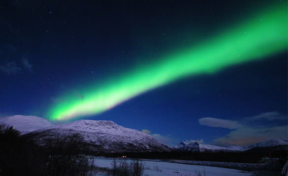 impressive display of the northern lights above a snow coloured mountain/