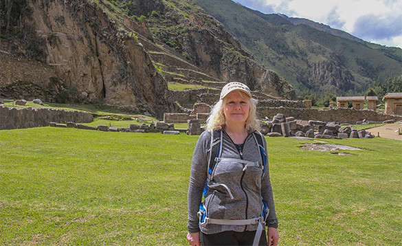 lady stood in front of stone ruins at the base of a mountain in Peru/