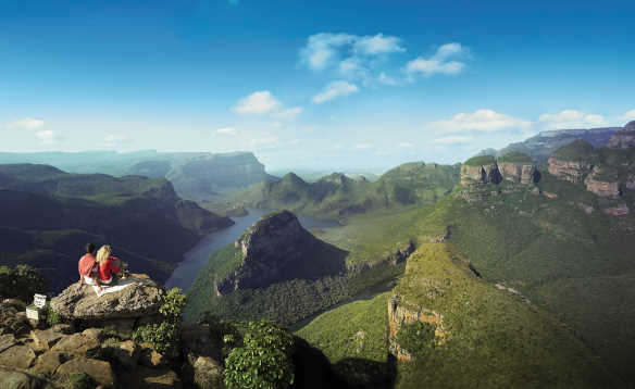 Couple sitting on rocks looking over a river flowing through Blyde River Canyon, South Africa/