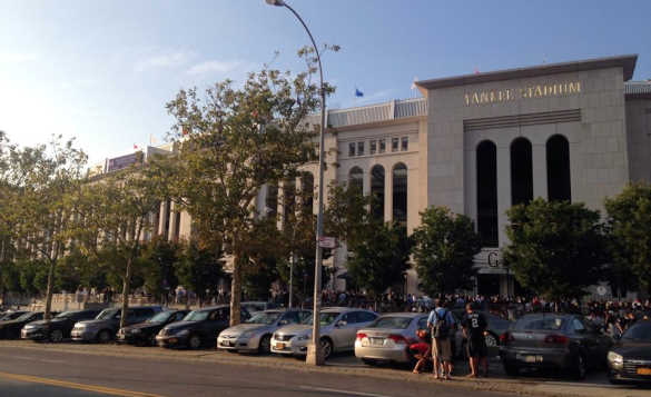 Cars parked outside the 'Yankee Stadium' and a large number of people can be seen in the background. /