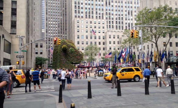 Busy New York street with yellow cabs driving past and lots of people walking around./