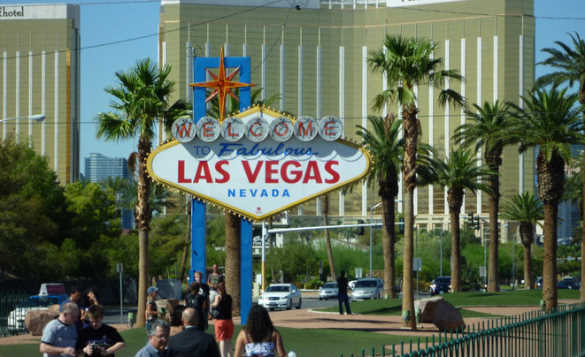 Famous 'Welcome to Fabulous Las Vegas' sign surrounded by palm trees and people. Buildings and cars can be seen in the background./