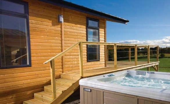 Hot tub next to a wooden self-catering lodge at Hoseasons Kessock Park Inverness/