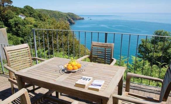 Table and chairs on a balcony with a view across the south Devon coastline/