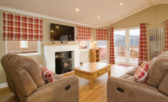 Living room with patio doors leading to a balcony at Hoseasons Loch Lomond Holiday Park/