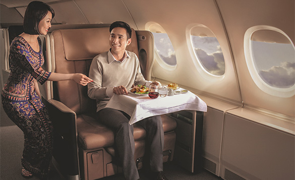 Passenger eating a meal on board a plane sitting in a luxury seat/