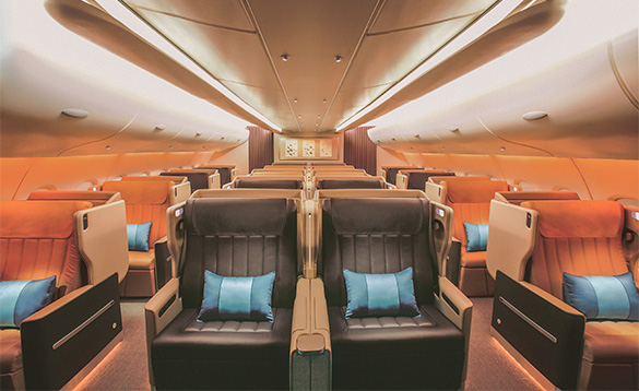 Inside of Singapore airlines plane with leather seats and blue cushions/