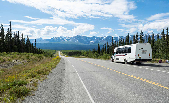Bus travelling on a road leading to snow capped mountains in the Yukon/