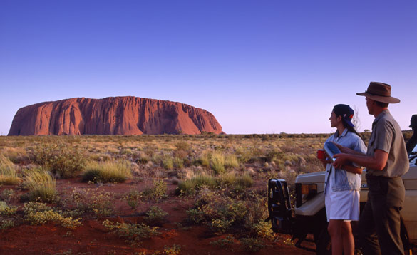 Man and lady stood next to a vehicle looking at Ayers Rock in Australia/