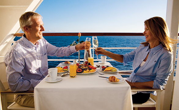 Couple toasting each other whilst enjoying food on the deck of an Azamara Cruise ship/