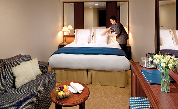 Maid making the bed in an interior stateroom on an Azamara cruise ship/