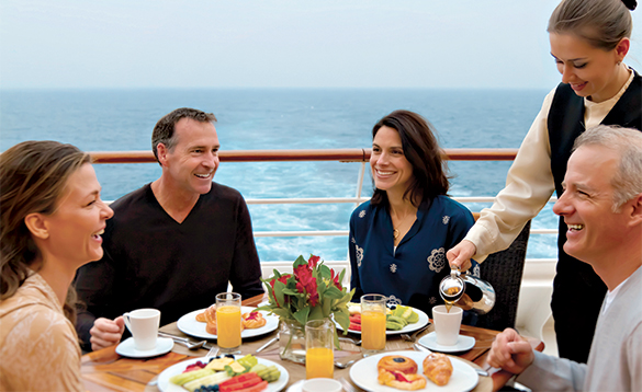 Waitress pouring coffee for four people enjoying breakfast on the deck of an Azamara Club cruise ship/
