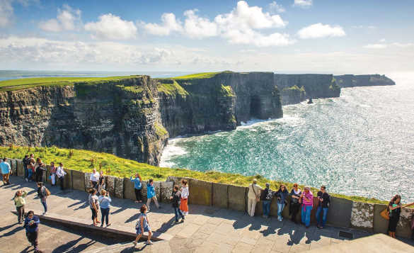 People standing looking across the Cliffs of Moher in Ireland/