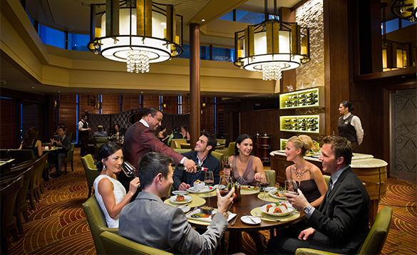 Waiter pouring wine for a group of diners in the Tuscan Grille on Celebrity Constellation cruise ship/