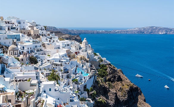 White houses on a hillside looking over blue seas/