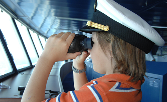 Boy wearing a Captains hat and looking through binoculars on the bridge aboard a Crystal Cruises ship/