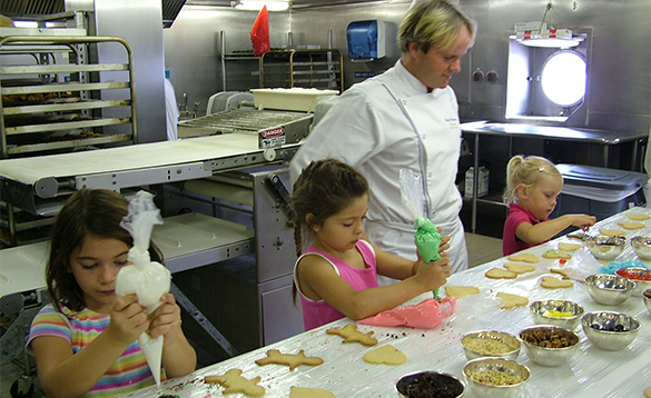 Chef watching children icing cookies onboard a Crystal Cruises ship/
