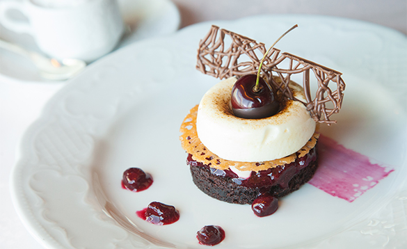 Chocolate cake dessert on a plate with cherries/