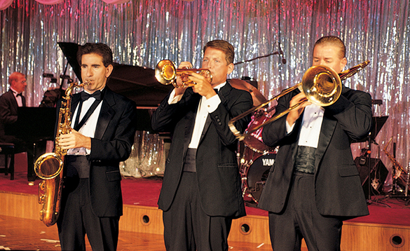 Musicians playing brass instruments and entertaining passengers in the Galaxy Lounge on a Crystal Cruises ship/