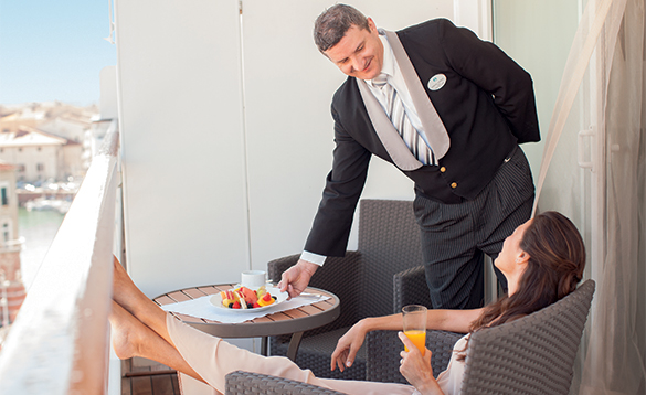 Butler serving breakfast to a lady on her cabin balcony/