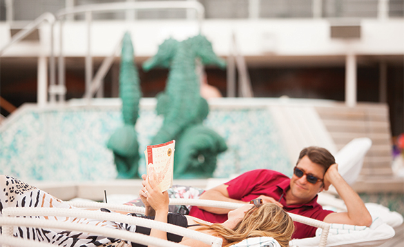 Couple relaxing on sunloungers reading/