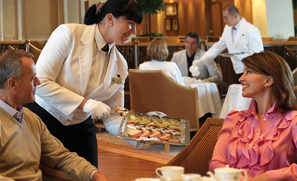 Waiters serving afternoon tea in the Queens Room onboard Cunard's Queen Elizabeth/