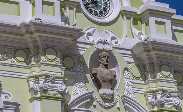 close up of a elaborately decorated building painted pale green and white with the bust of man in the middle/