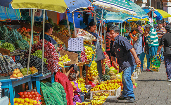 market street in Ecuador with stalls laden with fresh fruits and vegetables/