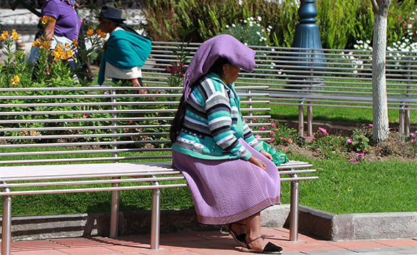 lady in Ecuador sitting on a bench on a hot sunny day/