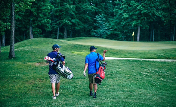 Two golfers walking along the fairway of a golf course/