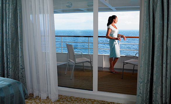 Lady with a glass of wine enjoying views from the balcony of her cabin on a Fred Olsen cruise ship/