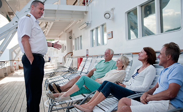 Passenger relaxing on sun loungers and chatting with the captain on board a Fred Olsen cruise ship/