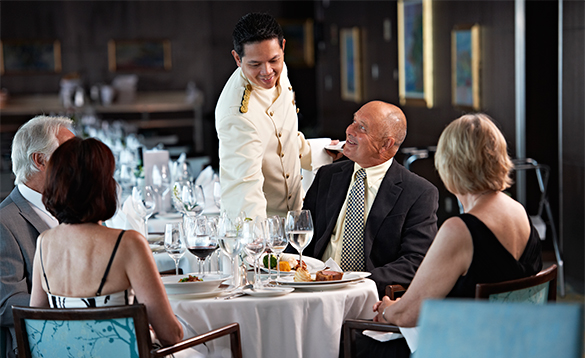 Waiter serving food to a group of people eating in the Balmoral Avon Restaurant on a Fred Olsen cruise ship/