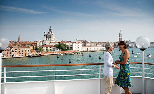 Two ladies on the deck of a cruise ship enjoying the view as the ship sails into Venice/
