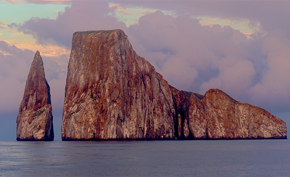 large rocky russet coloured island with smaller pointed rocky outcrop at the side/
