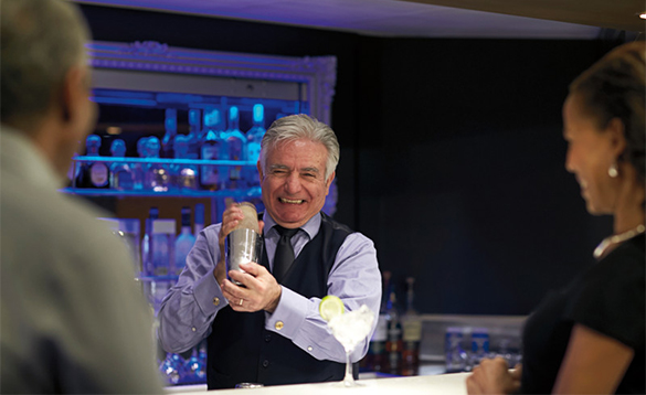 Barman mixing cocktails for a couple in the Gallery Bar on a Holland America cruise ship/