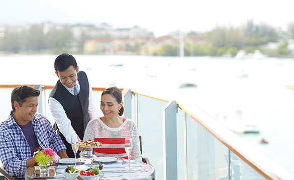 Waiter serving food to a couple sitting on their balcony onboard a Holland America cruise ship/