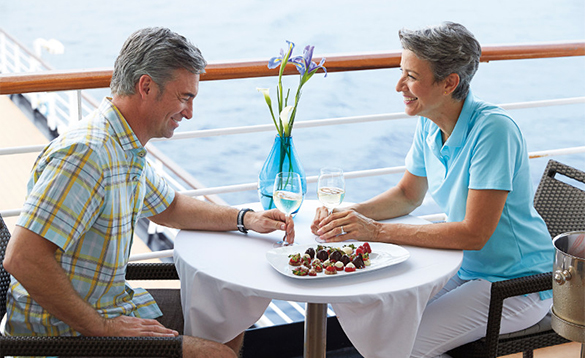Couple enjoying drinks on the deck of a Holland America cruise ship/