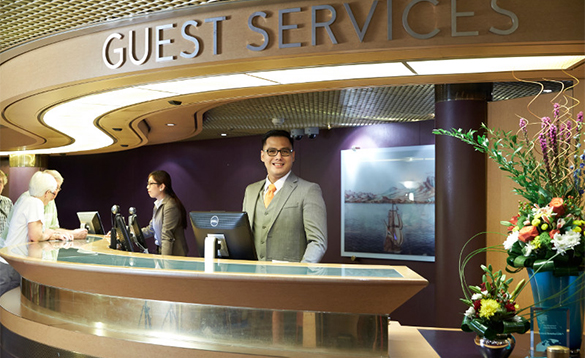 Staff member greeting passengers onboard a Holland America cruise ship/