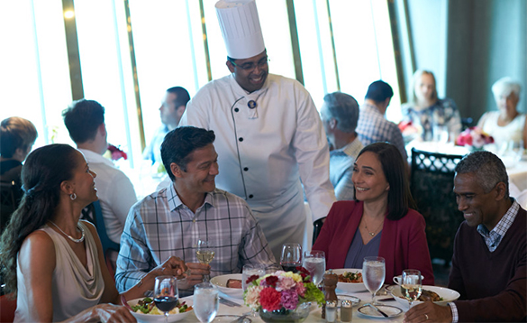 Passengers enjoying food onboard a Holland America cruise ship whilst chatting with the chef/