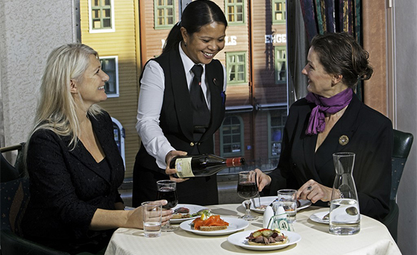 Waitress serving wine to two ladies eating lunch onboard a Hurtigruten cruise ship/
