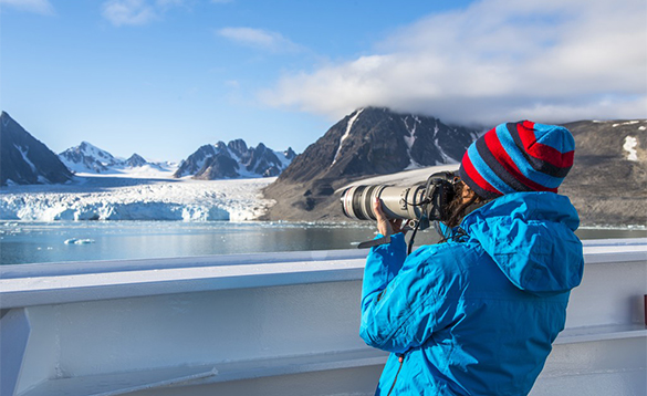 Lady taking a photograph of a glacier from a Hurtigruten Cruise ship/